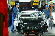 Factory workers check a car body on the assembly line at the Shanghai GM factory in Pudong October 14, 2004.