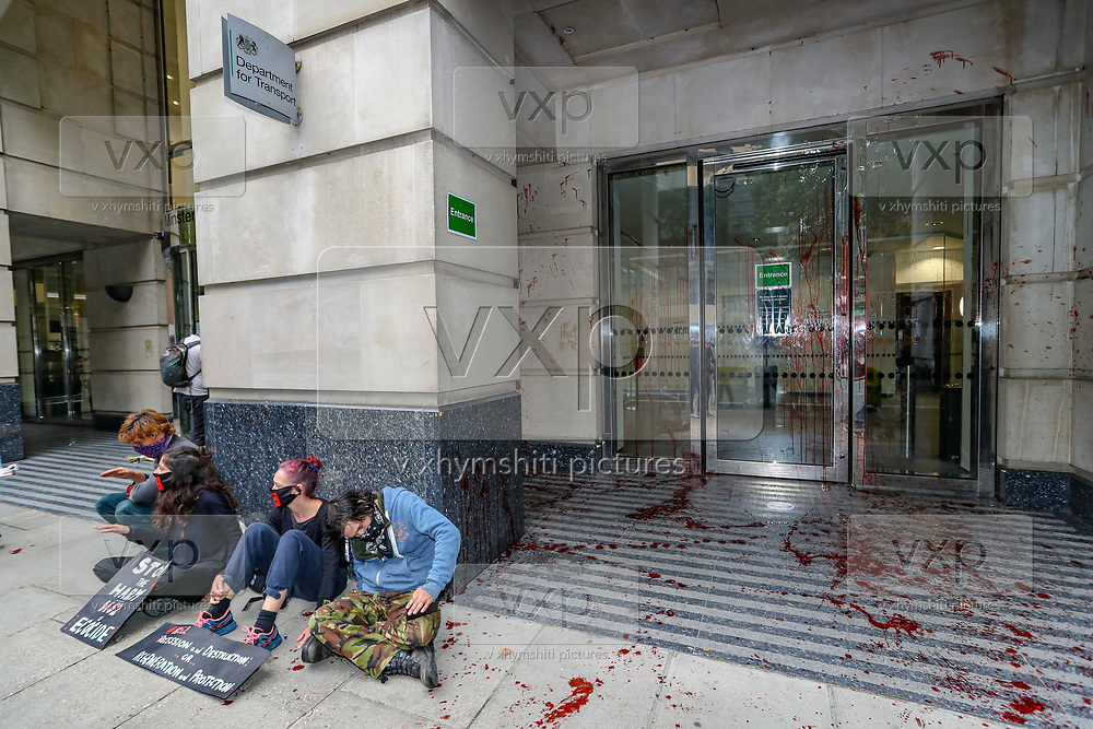 Extinction Rebellion activists group glued themselves outside Department for Transport entrance, meanwhile other activists pelted red colour at the Department for Transport's main entrance in Horseferry Road in central London on Friday, Sept 4, 2020. There are other Extinction Rebellion protests ongoing in London. Police closed Horseferry Road both ways as a group of protestors from Parliament Square marched towards Department for Transport demanding an end of HS2 construction. Environmental nonviolent activists group Extinction Rebellion enters its 4th day of continuous ten days protests to disrupt political institutions throughout peaceful actions swarming central London into a standoff, demanding that central government obeys and delivers Climate Emergency bill. (VXP Photo/ Vudi Xhymshiti)