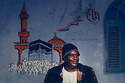 Hajj Omar infront of his house with a painting of the pilgrimage journey that earned him the title Hajj