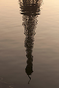 The iconic spire of the Eiffel Tower reflected in the water of the River Seine in Paris, France
