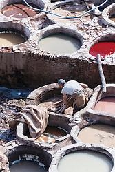 Man working in vats at the tanneries of Chouwara, Fes al Bali medina, Fes, Morocco