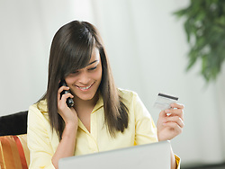 Young woman using credit card over the phone (Credit Image: © Image Source/ZUMAPRESS.com)