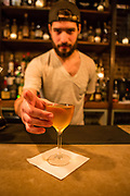 Astoria, NY - 8 December 2016. Bartender Cody Calderon mixing an Apothecary cocktail at The Bonnie. The Apothecary is made with Teeling small batch whiskey, Barr Hill Tom Cat gin, Cocchi Americano, pamplemousse liquer, and autmn spices.