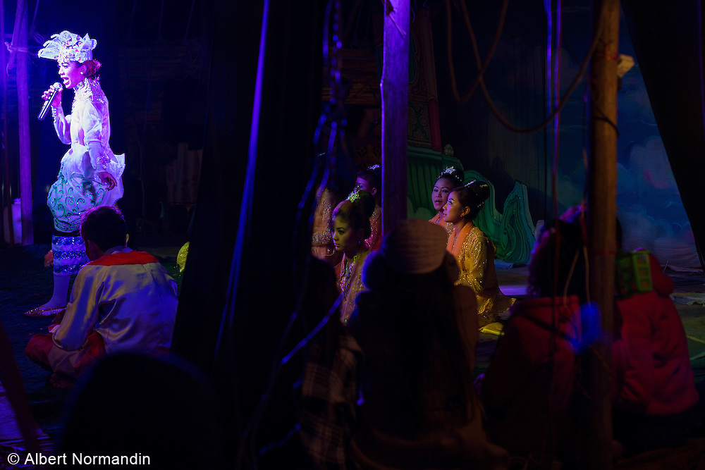 All night stage show at festival, performer singing in blue light, Monywa
