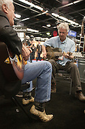 """January 21, 2016 - Anaheim, CA: Grammy award winning US blues musician Mike Dowling (gray shirt) and world touring US bluesman Doug Macleod (black jacket, jeans & snakeskin boots) jam at the National Resophonic booth during the NAMM Show, an annual trade show organized by the The National Association of Music Merchants (NAMM). <br /> <br /> The largest of its kind, NAMM features music instruments and products of every imaginable music-related item. National Resophonic was started in 1989 by Don Young and McGregor Gaines in a garage in Long Beach, CA. The two resurrected the legendary guitar company National String Instrument Corporation originally founded in 1927 by the Slovakian born John Dyoperra. These instruments called """"resonator guitars"""" were steel bodied with built in speaker cones that projected loud sound, good enough for live performances. Their unique sound became the preferred instrument of blues, Hawaiian and hillbilly musicians of the 1930s and are iconic of these musical genres. National went out of business in the 1950s due to the invention of the electric guitar. In 1990, Young and Gaines formed National Resophonic, a new company in San Louis Obispo, CA that produced excelent modern versions of the older guitars. Their guitars are in very high demand worldwide among guitarists from street performers to famed musicians like Keb' Mo', Bonnie Raiit, John Mellencamp and Eric Clapton. National currently produces nearly 2700 instruments per year, representing more than 50 different models. The waiting list to order one of their guitars can be several months. Young and Gaines sold their interests in the company which it is now owned by Eric Smith, an emplyee of National for 24 years. Sadly, Don Young passed away on June 15, 2016. (Torin Boyd/Polaris)."""