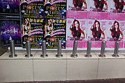 Metal stumps prevent people from sitting down or sleep rough on a ledge in the shopping district of Kowloon. Posters with young women advertise club nights and parties around Christmas time in Hong Kong.
