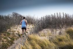 A man runs up a sand dune at Fistral Beach in Newquay, Cornwall.