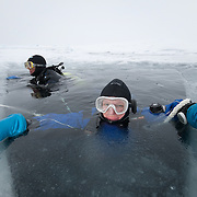 Heloise Chenelot waits for help to exit the ice hole she's been diving in. Arctic Ocean