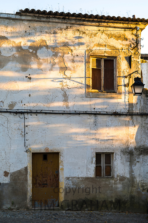 Old derelict white and yellow house in need of renovation work in Evora, Portugal