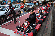 A parade of go-cart drivers in Christmas costumes sit in a traffic jam at the Shibuya crossing. Tokyo, Japan