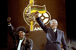 Nelson Mandela, with wife Winnie, gives the famous clench-fist saltue of the African National Congress to tens of thousands of fans who gathered to hear him at a concert in his honour at Wembley Stadium last night.