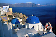 From a blue-domed Greek Orthodox Church in Oia village, view southeast across the ocean filled caldera to Imerovigli and Fira on Santorini Island, Greece, Europe. Geologic and human history of Santorini: Humans first arrived around 3000 BC on this volcano known in ancient times as Thira (or Thera). The island was a volcanic cone with a circular shoreline until 1646 BC, when one of earths most violent explosions blasted ash all over the Mediterranean, sunk the center of the island, launched tidal waves, and may have ruined the Minoan civilization 70 miles away on Crete. Remarkably, volcanic ash dumped onto the volcanos flanks actually preserved the village of Akrotiri and its 3600-year-old frescoes from the Minoan era. These are some of the earliest known examples of world art history, which you can now view in museums. In 286 BC, the volcano split off Thirasia (Little Thira) Island (to the West). The volcano began rebuilding, and in 197 BC the small center islet of Palia Kameni appeared. In 1707 CE, lava started forming Nea Kameni, the larger center island which erupted as recently as 1956 and caused a huge earthquake (7.8 on the Richter scale) which destroyed most of the houses in the towns of Fira and Oia. Fira and Oia have since been rebuilt as multi-level mazes of fascinating whitewashed architecture, attracting tourists from around the world.