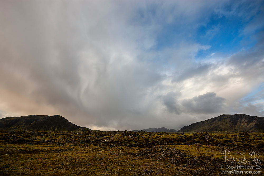 Late afternoon storm clouds develop over lichen-covered volcanic rocks and hills near Hveragerði in southern Iceland.
