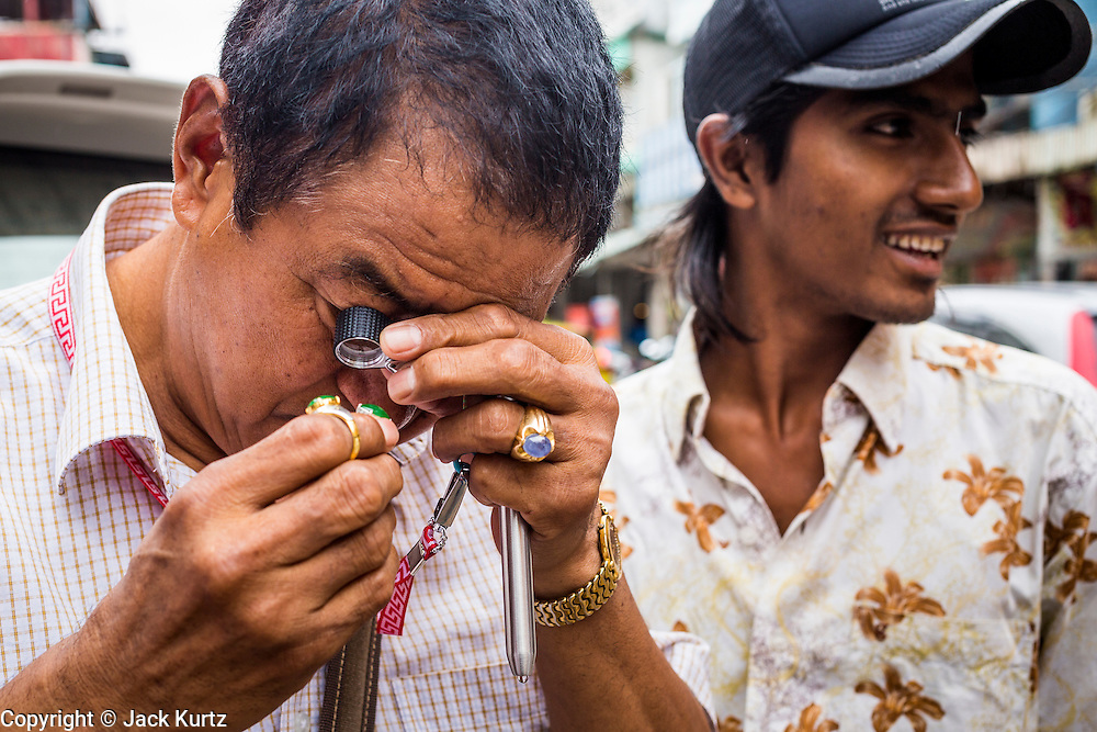 23 MAY 2013 - MAE SOT, TAK, THAILAND:  A Chinese gemstone buyer checks the quality of a stone being sold by a Burmese man in the Burmese gem market in Mae Sot, Thailand. There is a thriving business in buying and selling gems and precious stones in Mae Sot. Many of the gems are smuggled into Thailand from Myanmar. Fifty years of political turmoil in Burma (Myanmar) has led millions of Burmese to leave their country. Many have settled in neighboring Thailand. Mae Sot, on the Mae Nam Moei (Moei River) is the center of the Burmese emigre community in central western Thailand. There are hundreds of thousands of Burmese refugees and migrants in the area. Many live a shadowy existence without papers and without recourse if they cross Thai authorities. The Burmese have their own schools and hospitals (with funding provided by NGOs). Burmese restaurants and tea houses are common in the area.    PHOTO BY JACK KURTZ