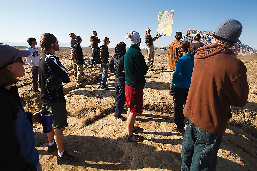 Geomorphology professor Robert Anderson (University of Colorado) discusses the geology of Factory Butte (visible in the background) to his students on a field trip to Utah.