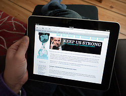 Man reading Wikileaks website on an iPad tablet computer