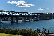 Cyclists pass along the walkway near the Iron Cove Bridge, Sydney, Australia,