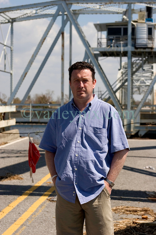 08 Sept 2005. New Orleans, Louisiana.  Hurricane Katrina aftermath. <br /> The Daily Mirror's Aidan McGurran in East New Orleans, where the tidal surge washed over the land and devastated homes and property. Aiden makes it to the furthest point east before the bridges are out.<br /> Photo; ©Charlie Varley/varleypix.com