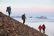 Grzegorz Karasinski (l-r), Rafal Flieger, Magdalena Puczko, and Lukasz Flieger take time off from work at the Polish Polar Station to hike the narrow ridge of Ariekammen for sunset views over Hornsund, Svalbard.