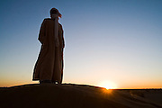 Camel guide Elhussein Sbiti stands on a dune at sunrise looking over the desert on a three-day camel trek to the remote sand dunes of Erg Zehar, near M'hamid in the Moroccan Sahara. Sbiti, like many berber nomads in the region, has found opportunity in the new tourism trade burgeoning since the settling of tensions between Morocco and neighboring Algeria..