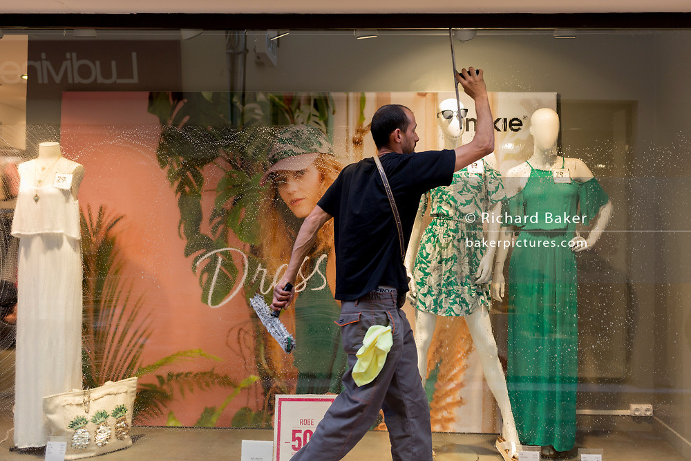 A window cleaner wipes soapy glass of a clothing retailer, on Pont de Marchands, on 23rd May, 2017, in Narbonne, Languedoc-Rousillon, south of France