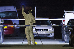 © Licensed to London News Pictures . 13/10/2015 . Eccles , UK . Scenes of Crime investigator on Gillingham Road , Eccles where it's reported a woman and a child were both shot this evening (12th October 2015) . It's reported the victims are a woman and her young son who were shot in the legs . It's the fifth shooting in Manchester in under a week . Photo credit : Joel Goodman/LNP
