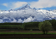 The majestic pyramid of the Monviso as seen from the countryside nearby Scalenghe in Piedmont, Italy. Taken a few minutes after the end of a strong rain storm on a day of mid April