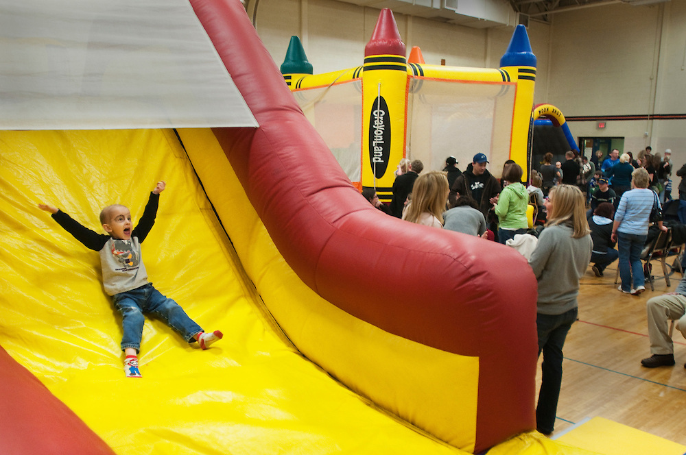Need to Caption...Matt Dixon | The Flint Journal..Adin Shrader has fun going down a slie during a fundraiser for his and Lauren Colombo's families. The two 4-year-olds have struggled with cancer