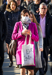 © Licensed to London News Pictures. 16/03/2020. London, UK. A commuter wearing a face mask and carrying an 'Eat Cake' bag walks across London Bridge this morning. New cases and fatalities resulting from the COVID-19 strain of the Coronavirus continue to be reported daily in the UK with major sporting fixtures cancelled and people advised to stay at home if they have a cough and high temperature. Photo credit: Vickie Flores/LNP