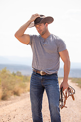 cowboy holding reins on a dirt road