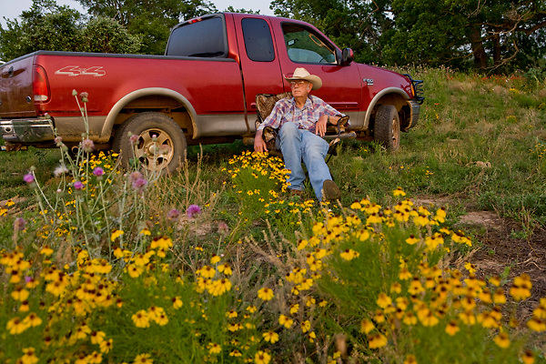 Stock photo of an older man sitting beside his pickup truck in the Texas Hill Country
