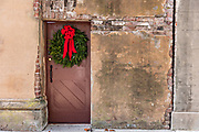 A Christmas wreath hangs from a wooden door on a historic home along King Street in Charleston, SC.