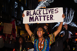 """London, November 26th 2014. A vigil for teenager Mike Brown who was shot dead by a policeman in Ferguson, Missouri this year, takes place outside the US embassy in London. Anti-racism and human rights campaigners called the 'emergency' protest following a court verdict that clears Police Officer Darren Wilson of murder. PICTURED: A woman's placard matches the crowd's chant """"Black lives matter!"""""""