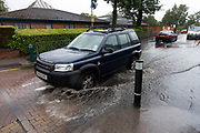 Cars drive through deep collected water following intense rainfall creating flash flooding in Birmingham, United Kingdom.