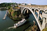 Fishing boat passing under arch bridge at Depoe Bay, worlds most narrow natural harbor entrance, Central Oregon Coast