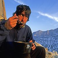 BAFFIN ISLAND, Nunavut, Canada. Mark Synnott (MR) eats freeze-dried dinner during Great Sail Peak big wall climbing expedition.