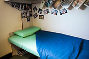 A prisoners bottom bunk bed, with family pictures up on the wall. HMP/YOI Portland, Dorset. A resettlement prison with a capacity for 530 prisoners. Portland, Dorset, United Kingdom.