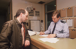 Man giving details to police officer at police station,