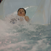 Taking a ride down the waterslide, Andre Sam, 12, enjoys the opportunity to get a little wet during the Relay for Life swim night event at the Gallup Aquatic Center in Gallup Friday.