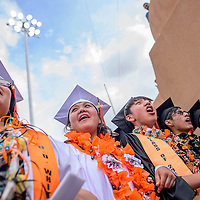 051614       Cable Hoover<br /> <br /> Gallup High School Seniors D.D. Whitegoat, left, Rachel Johnson, Patrick Skeets and others cheer as they make their way into the arena for their commencement ceremony at Red Rock Park Saturday.