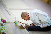 """30 JANUARY 2013 - PHNOM PENH, CAMBODIA:    A Cambodian woman wearing white mourning clothing prays for late Cambodian King Norodom Sihanouk in Phnom Penh. Sihanouk (31 October 1922- 15 October 2012) was the King of Cambodia from 1941 to 1955 and again from 1993 to 2004. He was the effective ruler of Cambodia from 1953 to 1970. After his second abdication in 2004, he was given the honorific of """"The King-Father of Cambodia."""" Sihanouk held so many positions since 1941 that the Guinness Book of World Records identifies him as the politician who has served the world's greatest variety of political offices. These included two terms as king, two as sovereign prince, one as president, two as prime minister, as well as numerous positions as leader of various governments-in-exile. He served as puppet head of state for the Khmer Rouge government in 1975-1976. Most of these positions were only honorific, including the last position as constitutional king of Cambodia. Sihanouk's actual period of effective rule over Cambodia was from 9 November 1953, when Cambodia gained its independence from France, until 18 March 1970, when General Lon Nol and the National Assembly deposed him. Upon his final abdication, the Cambodian throne council appointed Norodom Sihamoni, one of Sihanouk's sons, as the new king. Sihanouk died in Beijing, China, where he was receiving medical care, on Oct. 15, 2012. His cremation is scheduled to take place on Feb. 4, 2013. Over a million people are expected to attend the service.        PHOTO BY JACK KURTZ"""
