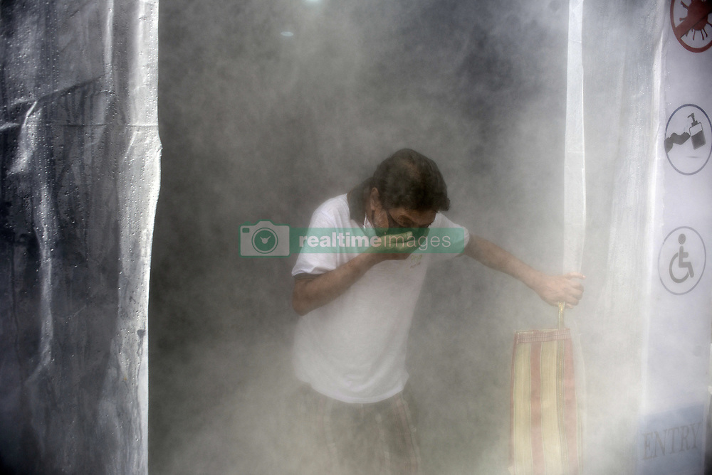 A man covering his mouth comes out of a sanitisation machine installed at a market in Kolkata midst the 2nd phase of lockdown in India due to covid 19 pandemic. This is to curb the spread of Covid 19 in the country. The second phase is handled with more strict rules by the administration. Kolkata, West Bengal, India, April 28, 2020. Photo by Arindam Mukherjee/ABACAPRESS.COM