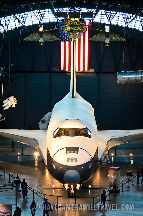 Wide shot of the space shuttle Enterprise on display at the Smithsonian National Air and Space Museum's Udvar-Hazy Center, a large hangar facility at Chantilly, Virginia, next to Dulles Airport and just outside Washington DC. Above the space shuttle hangs a satellite.
