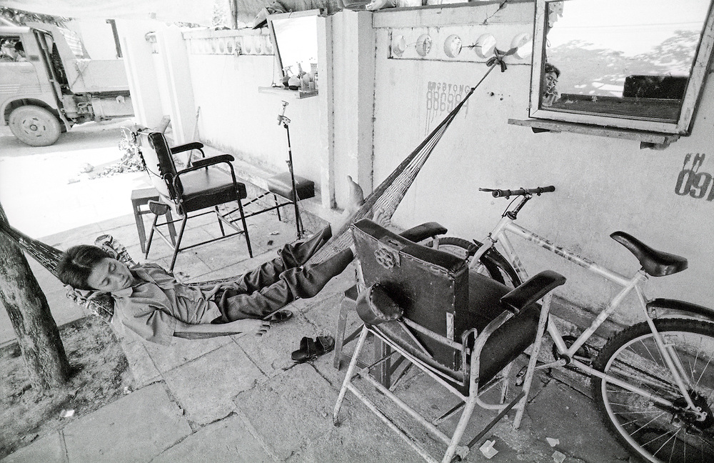 On a hot, lazy afternoon in Nha Trang, Vietnam a Vietnamese man sleeps in his open air barber shop