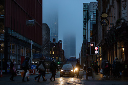 © Licensed to London News Pictures . 24/01/2019. Manchester , UK . Fog shrouds the upper floors of the Beetham Tower and the West Tower of Deansgate Square on Deansgate in Manchester City Centre , as commuters head to work this morning (Thursday 24th January 2019) . Photo credit : Joel Goodman/LNP