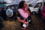 A Romany girl smokes a cigarette. Romany Gypsies at Appleby Fair, Cumbria. The most important annual Gypsy horse fair whre Romany Gypsies and travelers meet to trade their wares...English Romany Gypsies traditionally traveled the country roads camping nearby towns and villages, choosing the grassy roadside banks, where they tethered their horses, or in farmer's fields, when they were allowed. Travelling in bowtop wagons drawn by horses, and before that with tents, sometimes with horse drawn carts or just by foot. Often they worked as casual agricultural labourers, doing the seasons work. They also could earn their living in different ways, sometimes selling their wares, brass, tin, wood and cloth, such as embroidered cloths or lace, telling fortunes, music and dancing, and through crafts skills in basket making, plaiting chair bases, sharpening knives,  They would make fires from old wood, cleaning up after them when they moved on. There were several horse fairs, notably Appleby in Cumbria and Stow-on-Wold in the Cotswolds where they trade and sell horses, some traditions which keep to this day.
