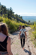 A group of young adults from Australia and Switzerland walk downhill toward the town of Blagaj, in Bosnia and Herzegovina, after visiting the fortress ruins above the town.