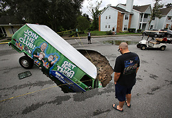 A van remains in a sinkhole on Monday, September 11, 2017 that opened up at the Astor Park apartment complex in Winter Springs, FL, USA, during Hurricane Irma's passing through central Florida Sunday night. The glass on the ground is the window that the driver punched out to extract himself after driving into the sinkhole. Photo by Joe Burbank/Orlando Sentinel/TNS/ABACAPRESS.COM