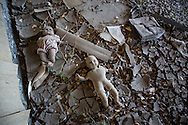 Blighted house in New Orleans lower 9th Ward with dolls on floor covered in dry mud.