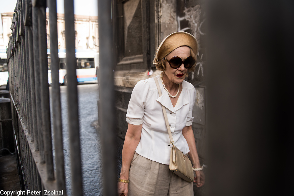 An elderly women is walking on the street with awesome style in Palermo, Sicily, Italy.